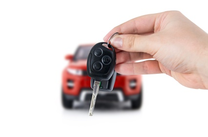 Hand holding keys to new red car. Buy or selling business composition